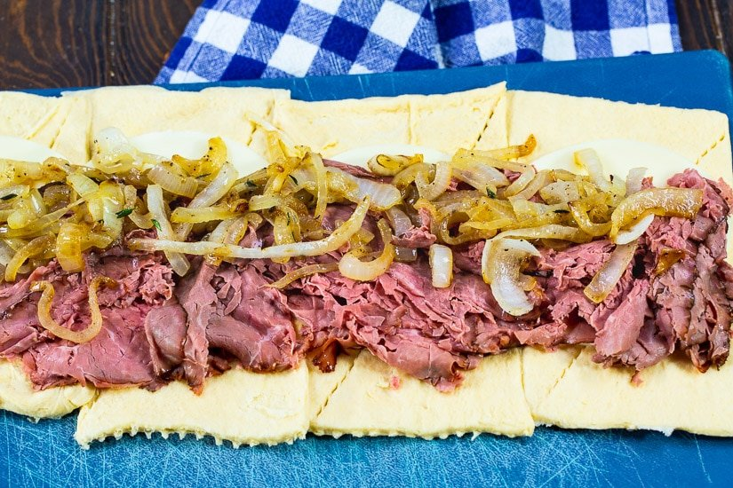 Roast beef and onions spread out on crescent roll dough.