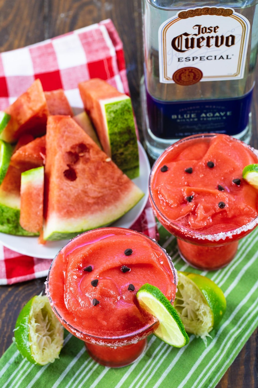 Two Watermelon Margaritas, plate of watermelon, and bottle of tequila.