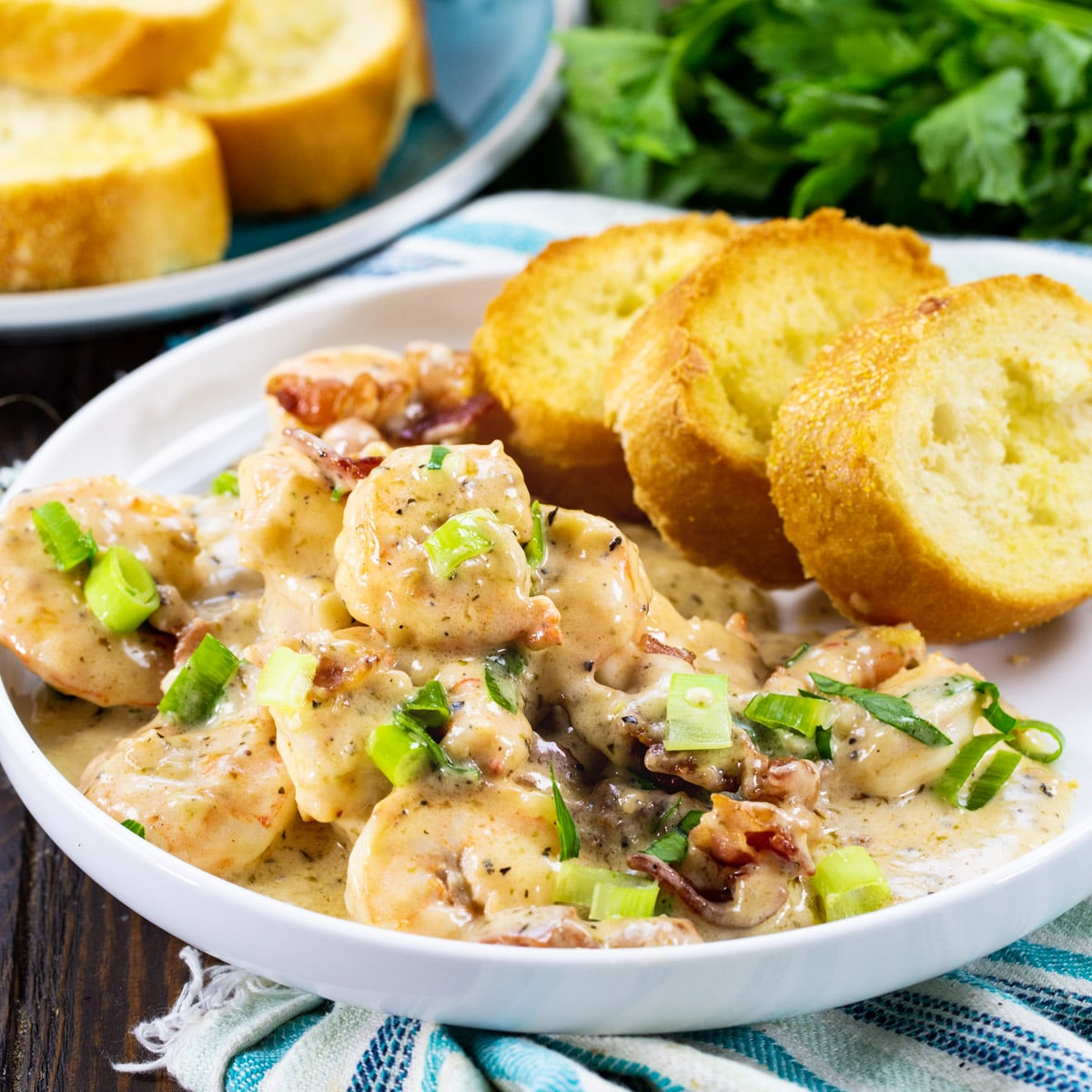 Garlic Shrimp with Creamy Parmesan Sauce with toasted baguette slices on a plate.