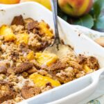 Gingersnap Peach Crisp in a white baking dish.