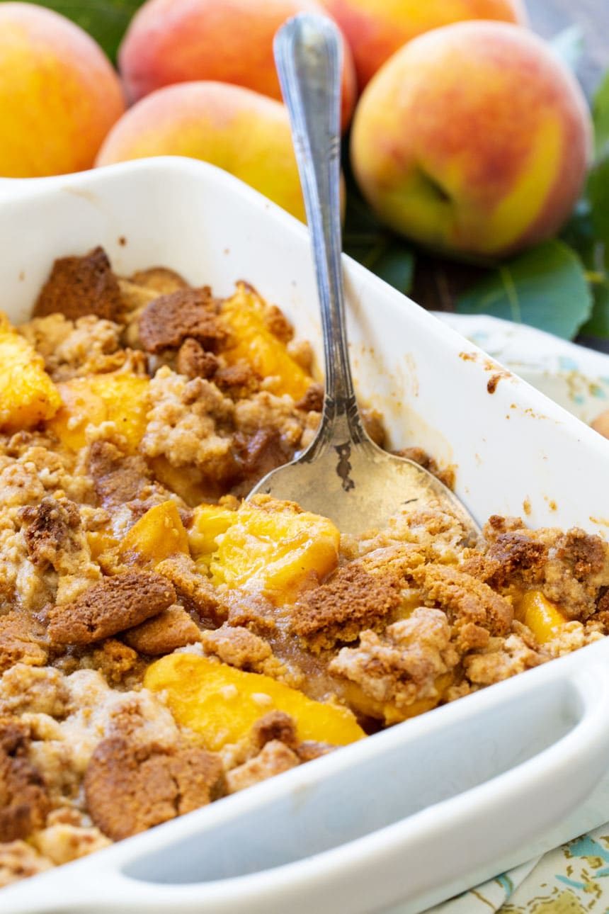 Peach Gingersnap Crisp in white baking dish with serving spoon.