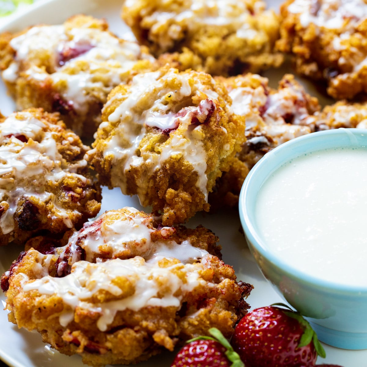 Glazed Strawberry Fritters on a plate with bowl of glaze.