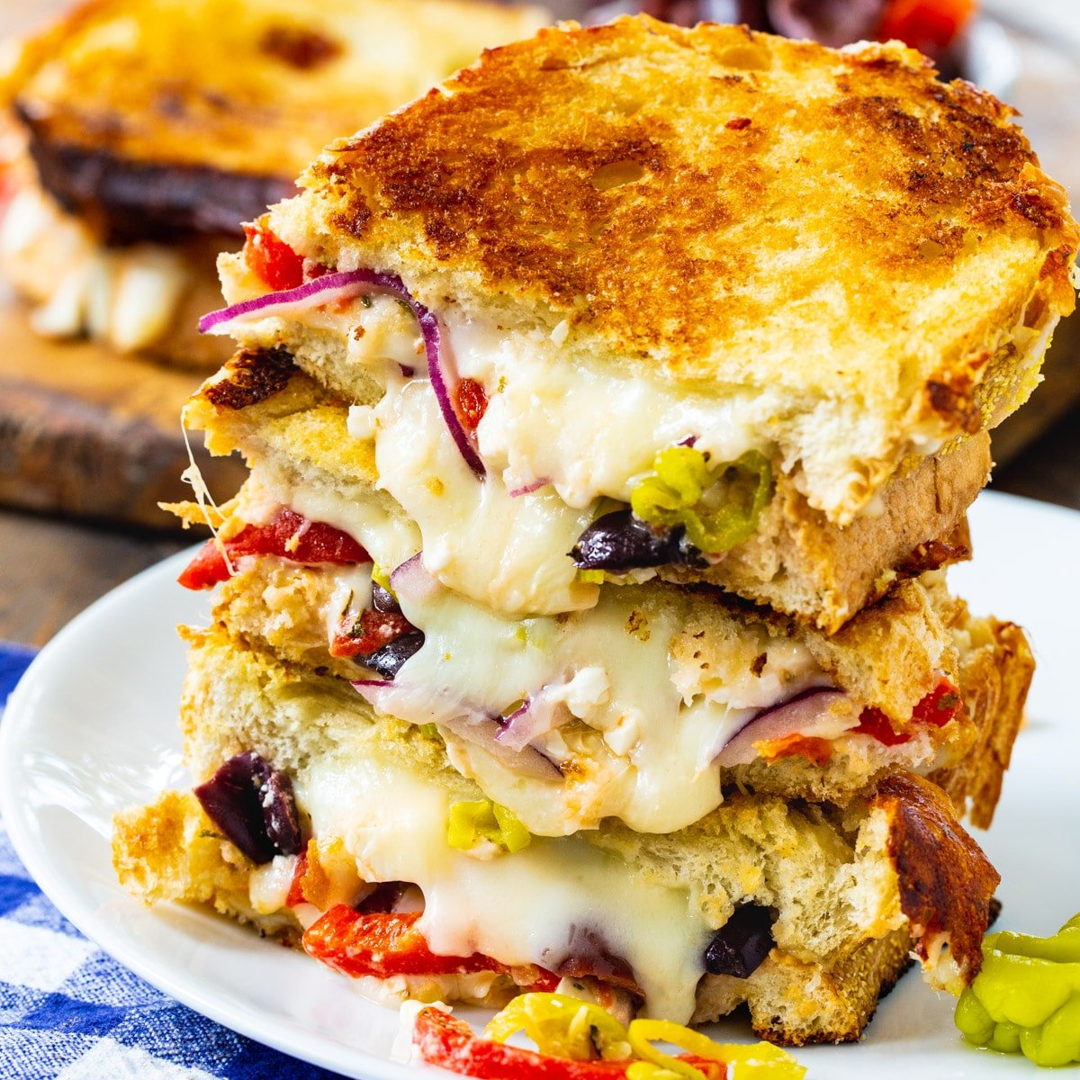 Greek Grilled Cheese halves stacked on a plate.