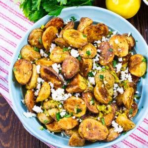 Greek Potatoes in a light blue bowl.