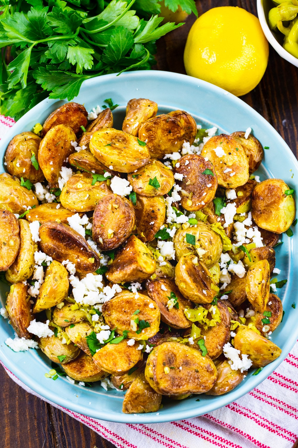 Greek Potatoes in a bowl surrounded by parsley and lemons.