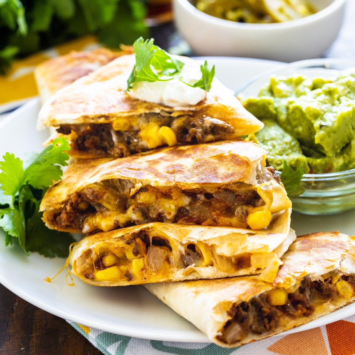 Ground Beef Quesadillas cut into wedges and piled on a plate.