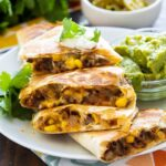 Quesadillas with cheesy ground beef filling on a white plate