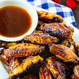 Wings on a plate with a bowl of glaze.