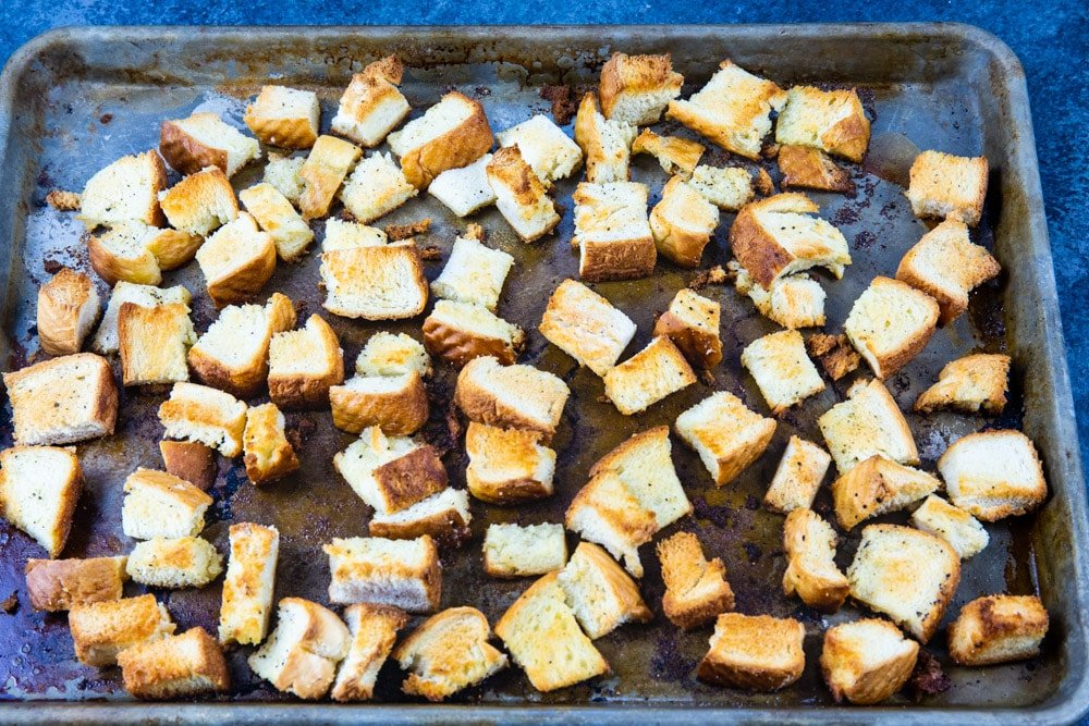 Toasted bread cubes on baking sheet.