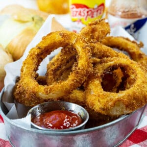 Hot Sauce Marinated Onion Rings in a serving dish with ketchup.