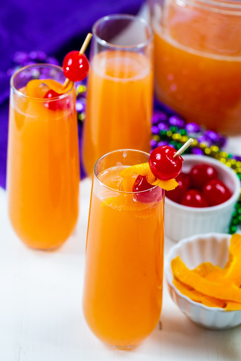 Mimosas in glasses surrounded by Mardi Gras beads.