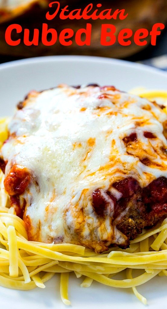 Close-up of Cubed Beef coveered with cheese on spaghetti.