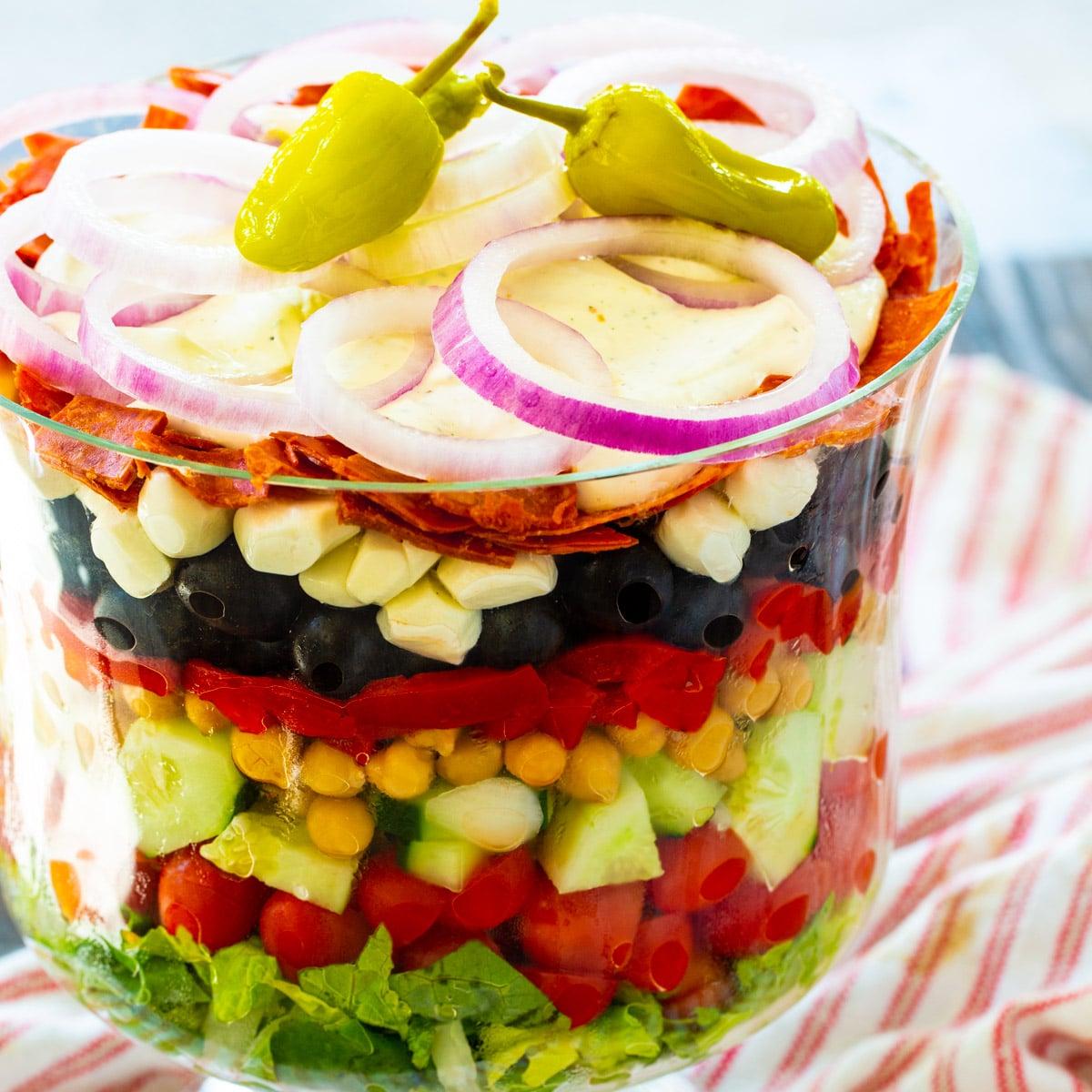 Italian Layered Salad in a trifle bowl.