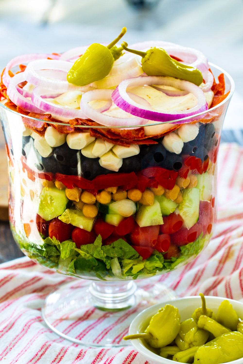 Italian Layered Salad in a glass trifle bowl with a small bowl of pepperoncini peppers in front.