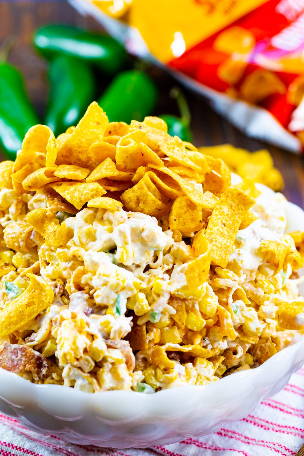 Jalapeno Popper Corn Frito Salad in white serving bowl with jalapenos in background.