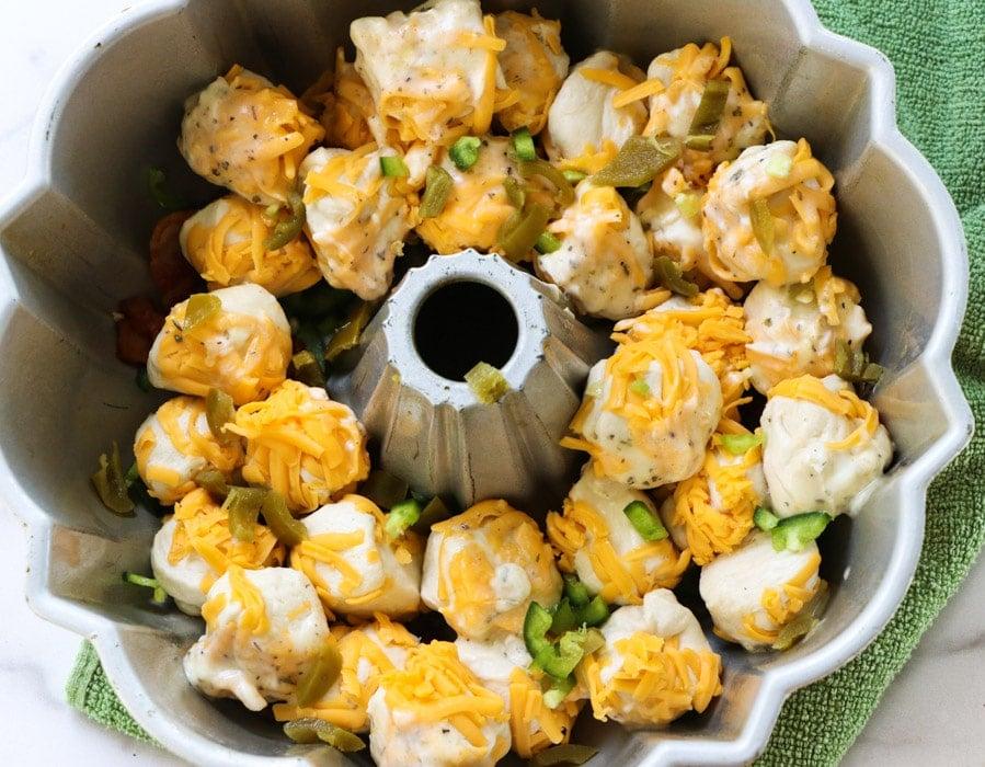 Biscuit balls coated in cheese in bundt pan.