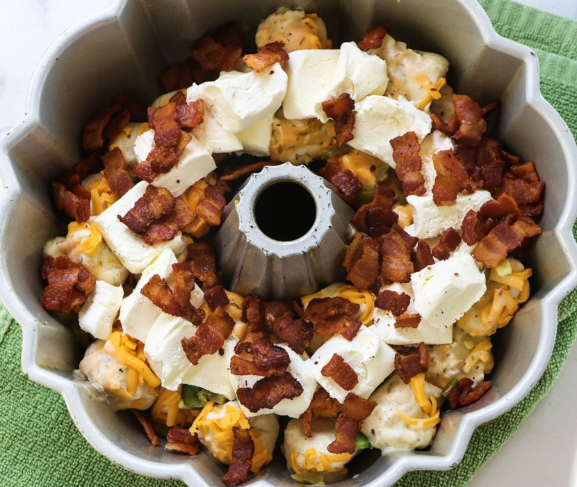 Cream cheese pieces and bacon placed on top of biscuit pieces.