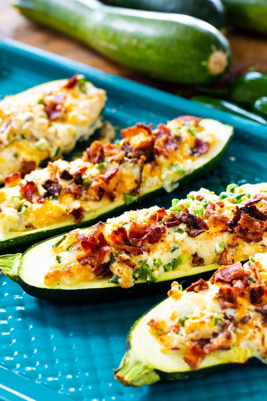 Jalapeno Popper Zucchini Boats on baking sheet with fresh zucchini in background.