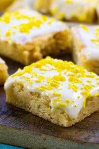 Lemon Cookie Bars topped with yellow sprinkles on a wood cutting board.