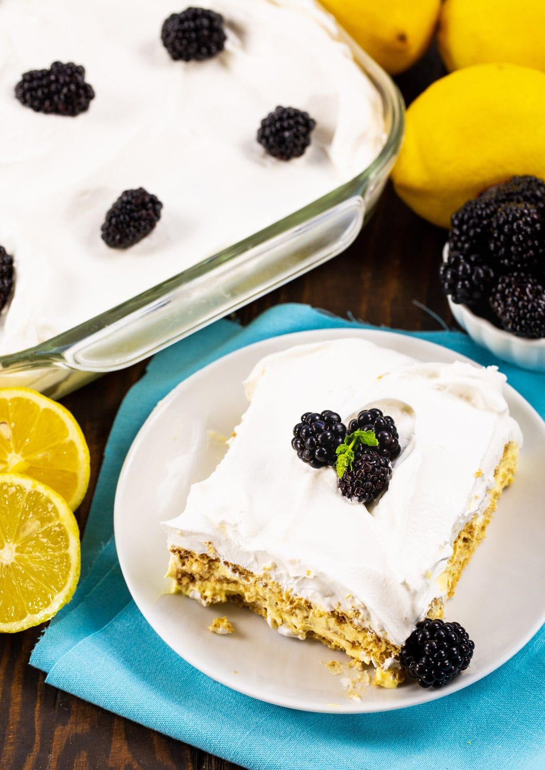 Slice of Icebox Cake on a plate surrounded by lemons and rest of the cake.