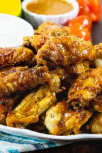 Mango Habanero Chicken Wings on a plate with a bowl of dressing.