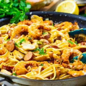 Pasta with shrimp and andouille in a skillet.