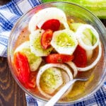 Marinated Cucumber, Tomato, and Onion Salad in a glass bowl.