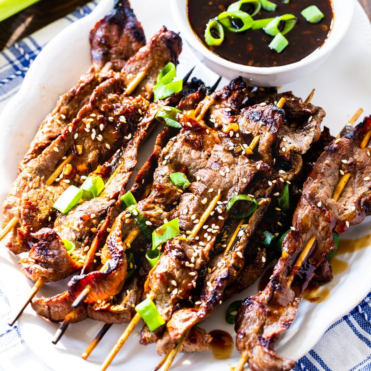 Marinated Steak Skewers with Korean BBQ Sauce on a white serving plate.