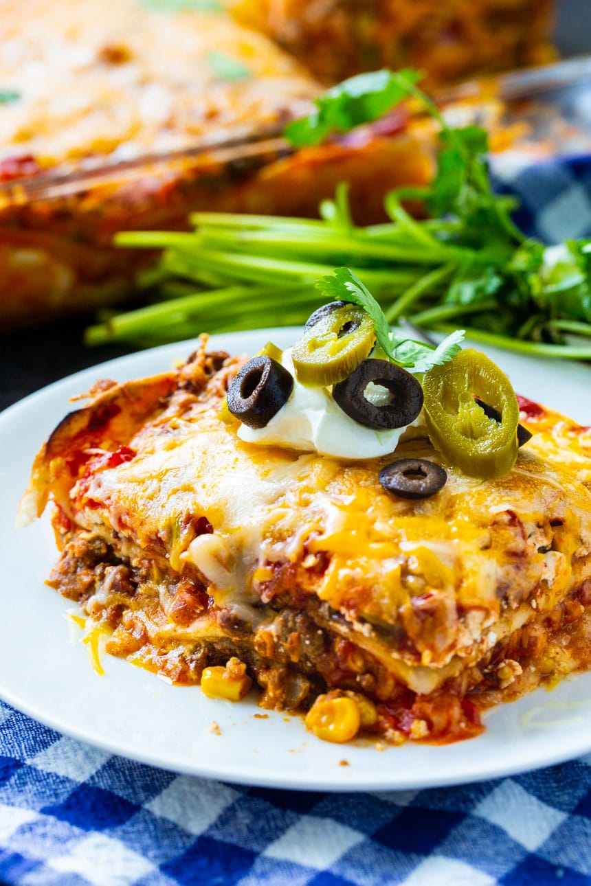 Lasagna on a plate with bunch of lasagna in background.