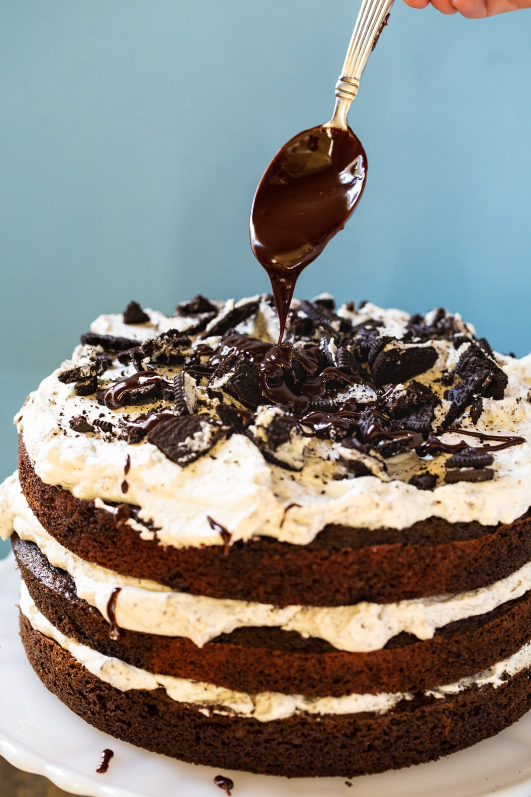 Spoon drizzling chocolate on Mississippi Mudslide Cake.