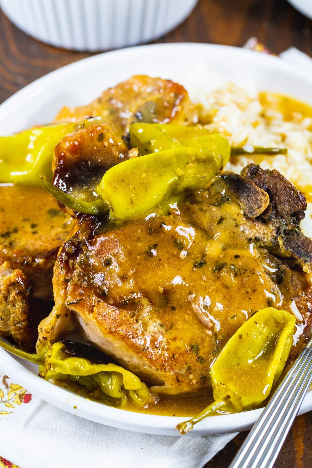 Pork chops with pepperoncini peppers on a plate.