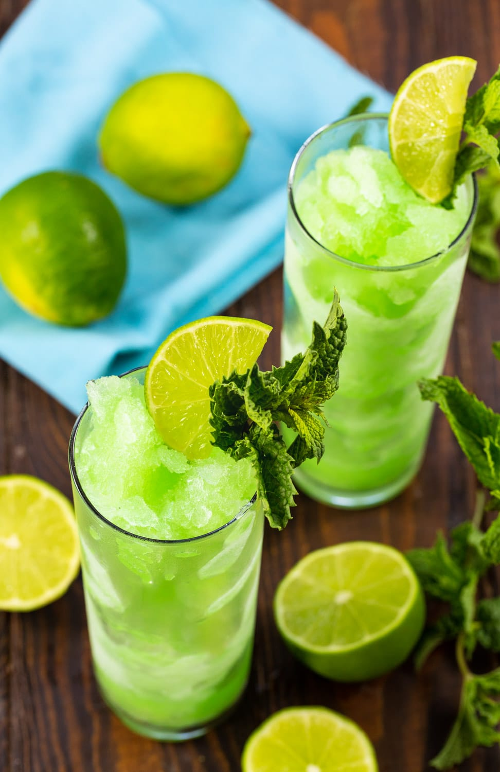 Two glasses filled with Mojitos with lime halves surrounding them.