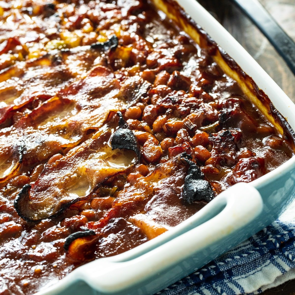 Molasses Baked Beans topped with bacon in a baking dish.