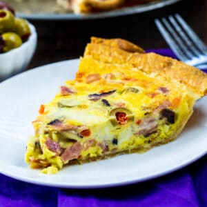 Slice of Muffaletta Quiche on a white plate.