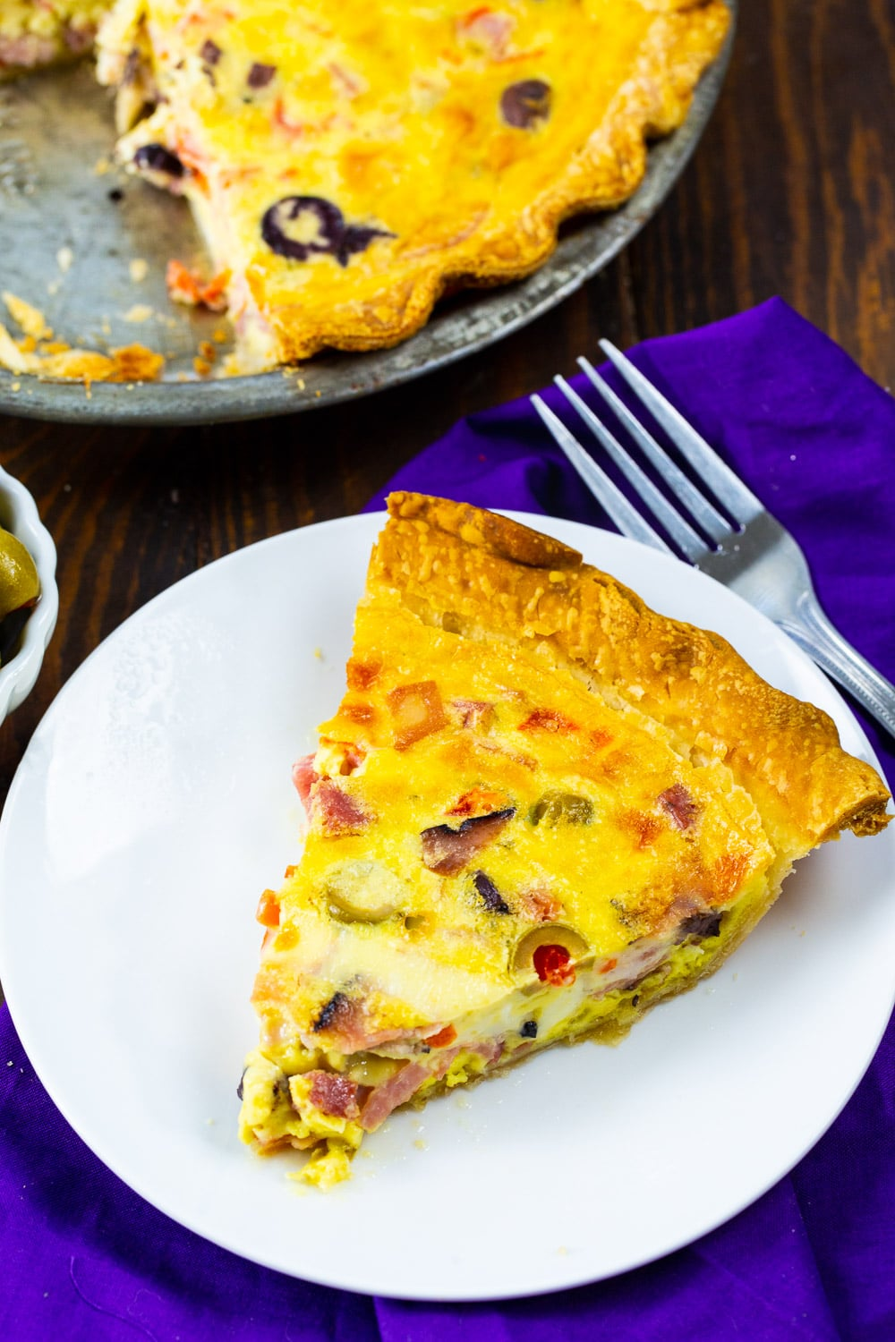 Quiche in a pie pan and a slice on a plate.