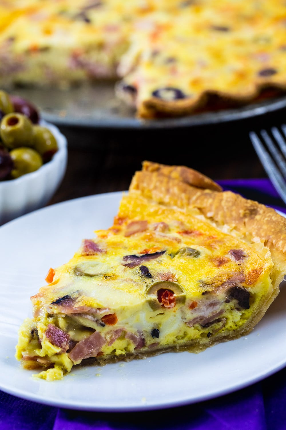 Slice of Muffaletta Quiche on a plate.