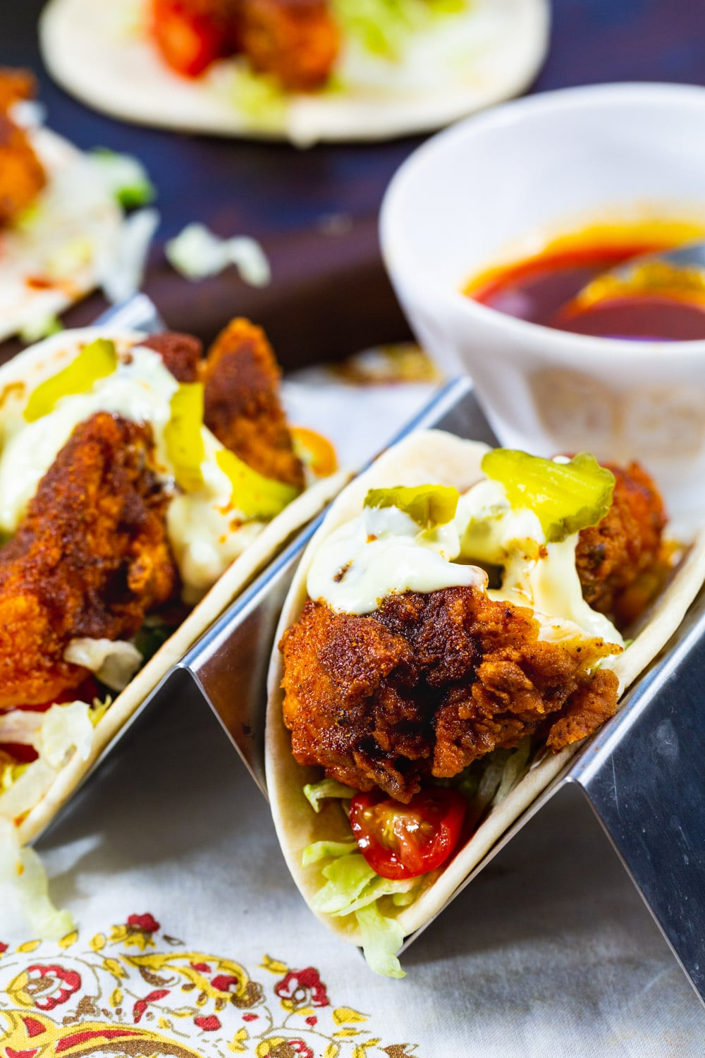 Fried Chicken Tacos with hot sauce topped with dill pickles.