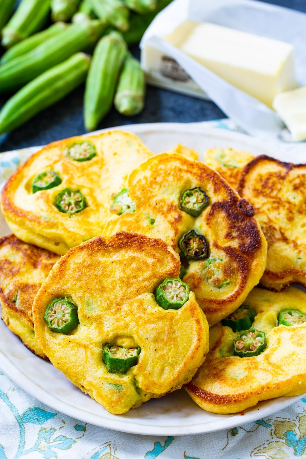 Hoecakes with okra on plate with okra in background.
