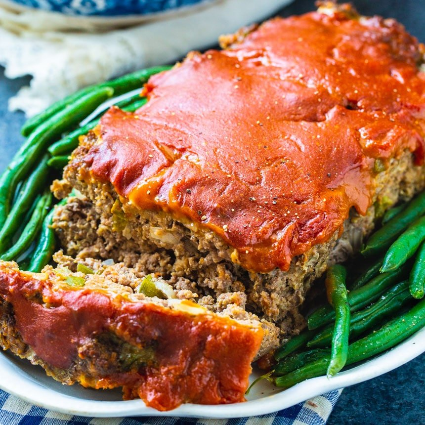 Meatloaf on serving plate with green beans.