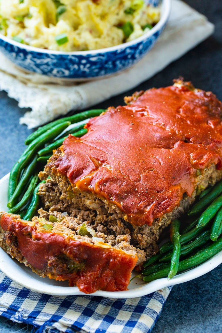 Meatloaf on plate with green beans and mashed potatoes in background.