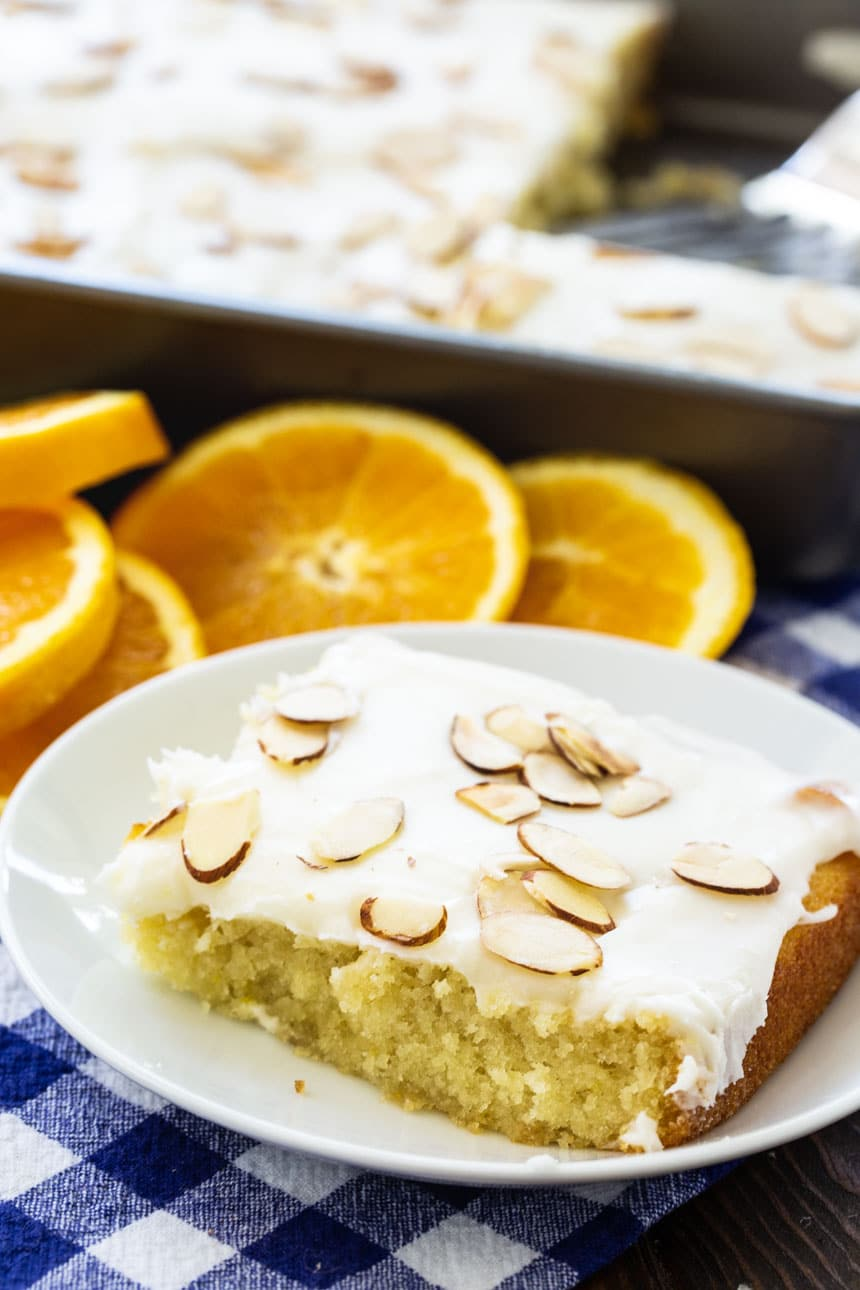 slice of sheet cake on a white plate with orange slices in background.