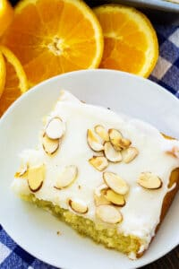 Slice of Orange Almond Sheet Cake on a plate surrounded by orange slices.