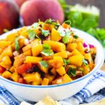 Peach Salsa in a bowl surrounded by fresh peaches and cilantro.