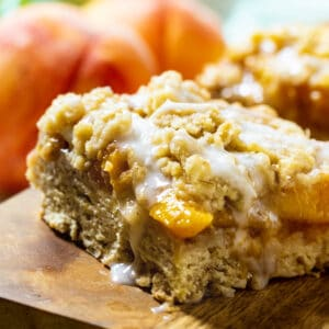 Peach Cobbler Bars with fresh peaches in background.