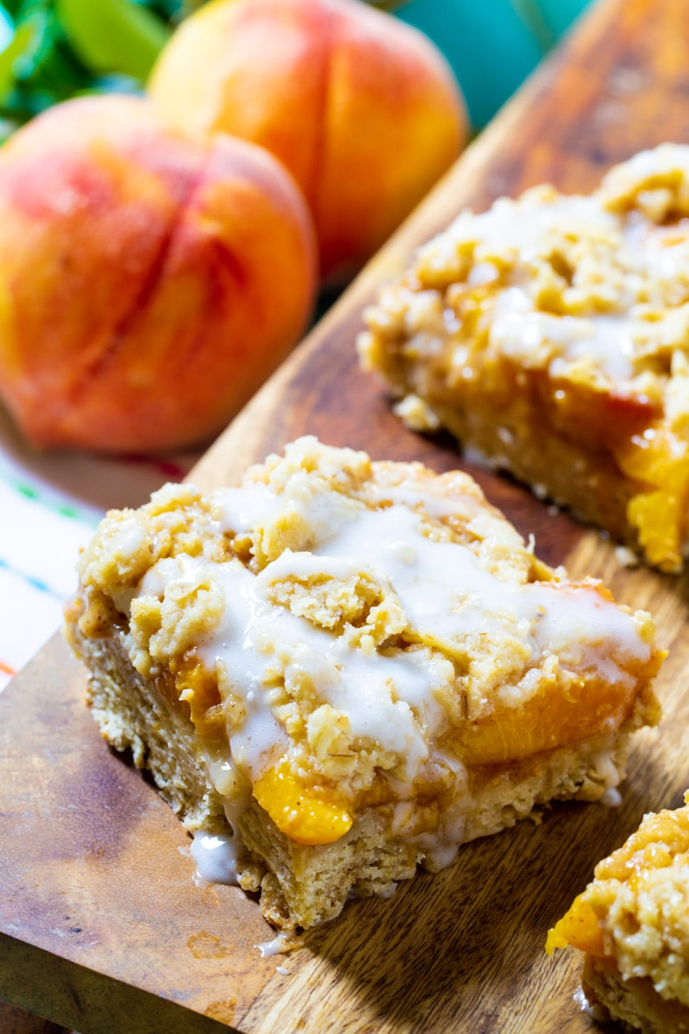 Peach Cobbler Bars covered with glaze on a wodden board.