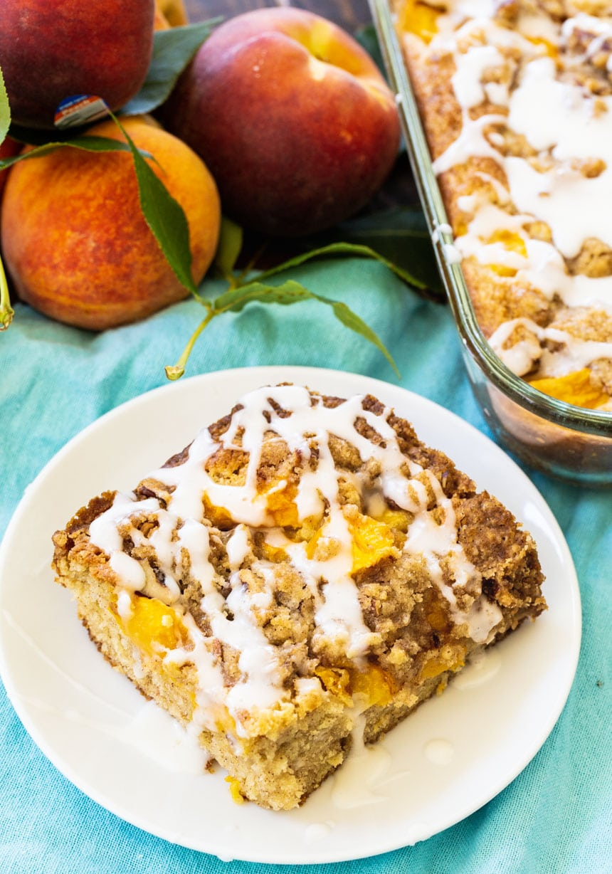 Peach Crisp Coffee Cake slice on a plate with peaches in background