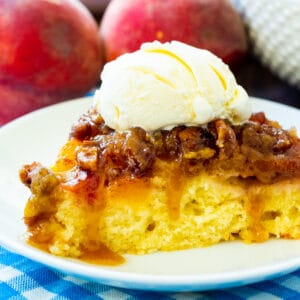 Slice of Peach Praline Upside Down Cake topped with ice cream.