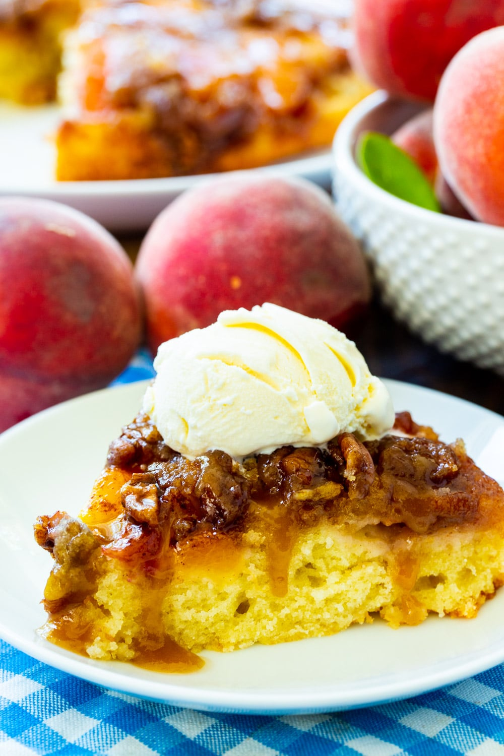 Peach Praline Upside Down Cake slice on a plate surrounded by fresh peaches.