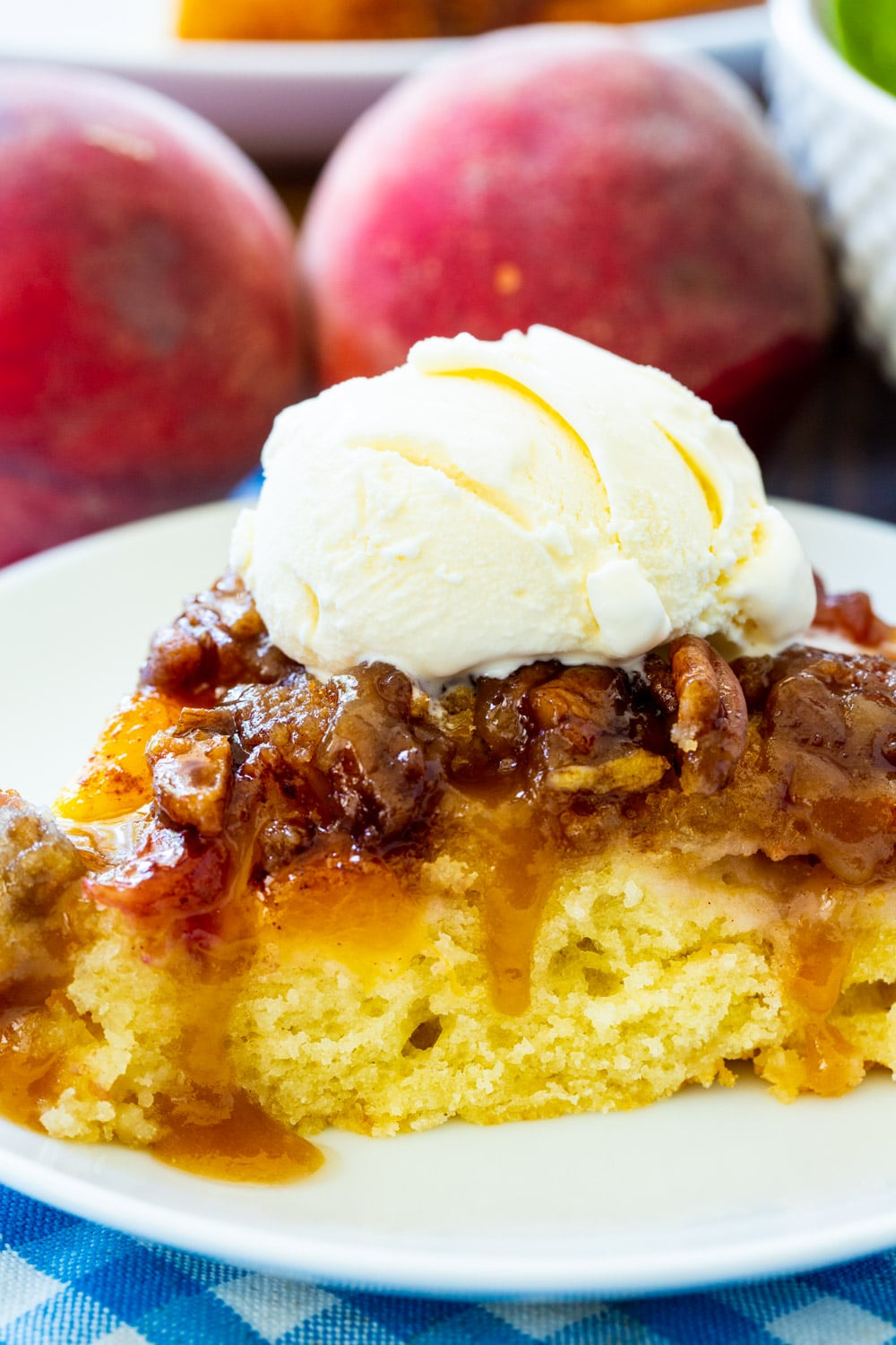 Close-up of slice of Peach Praline Upside Down Cake topped with vanilla ice cream.