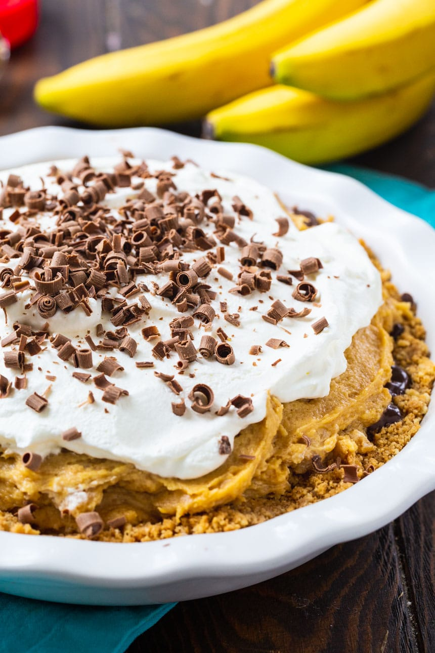 Peanut Butter Banana Pie in a white pie plate with bananas in the background